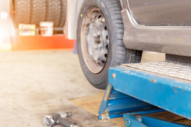 Mechanic fixing the wheel alignment device onto a car wheel of new tire replacement
