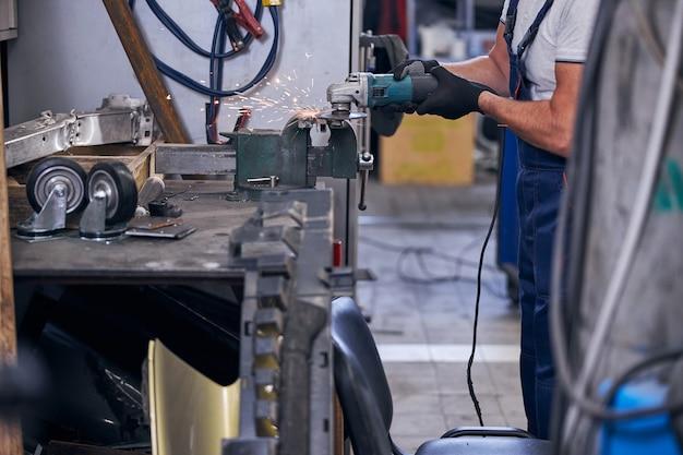 ガレージで自動車の金属部品を研削するメカニック