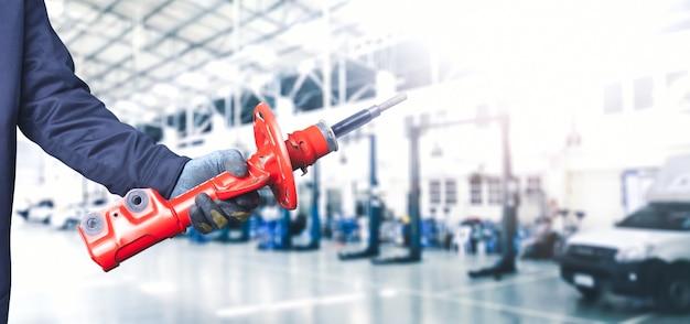 Рука механика, держащая передний амортизатор автомобиля в ремонтном гараже