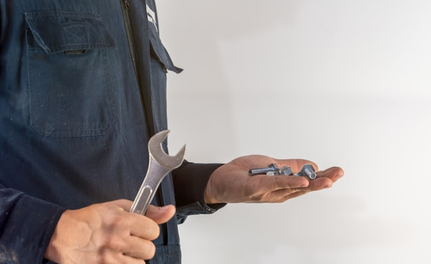 Mechanic hand holds nuts and spanner tool for industrial maintenance