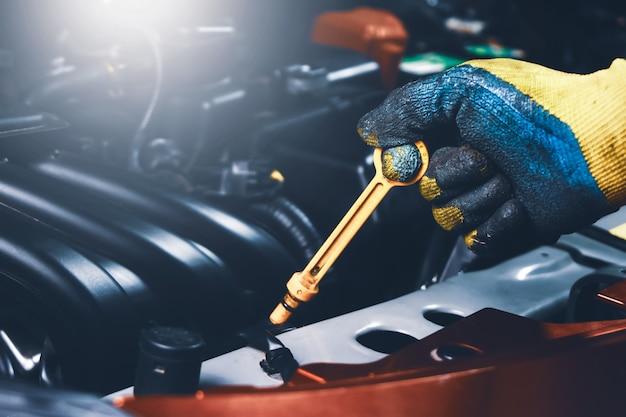 Рука механика, вытягивая масляный щуп двигателя автомобиля для проверки уровня масла