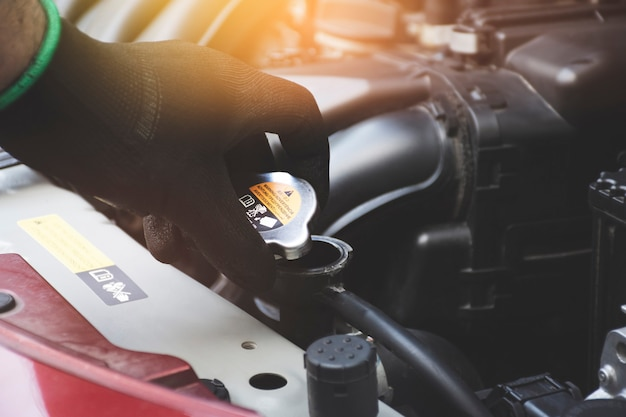 Mechanic hand was opening the radiator cap to check the coolant level of the car radiator