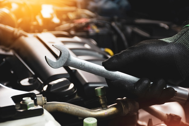 The mechanic hand wearing black gloves holding open-end wrench with a sunlight and engine blurred