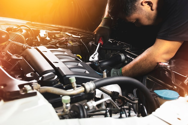 The mechanic hand wearing black gloves is fasten the bolt with the socket wrench to repairing of the car engine