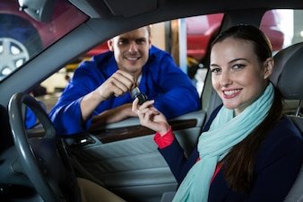 Mechanic handing over key to customer