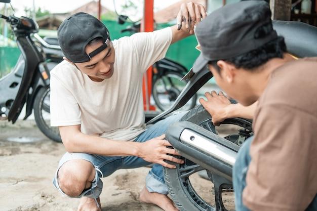顧客がスクーターバイクを修理するのを助ける整備士