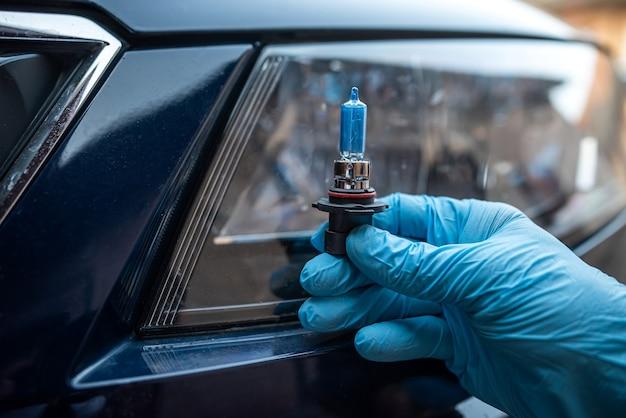 백그라운드에서 헤드라이트 자동차 수리를 위한 정비공 홀드 자동차 할로겐 전구