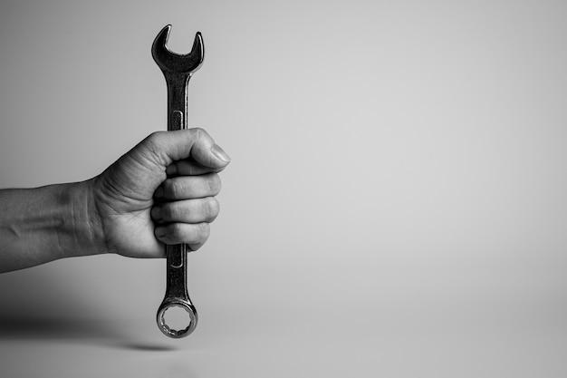 Механик держит гаечный ключ в руке.