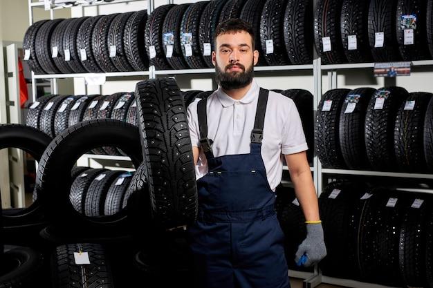 自動車修理サービスと自動車店でタイヤを持ってホイールタイヤを見せている整備士、自動車修理ガレージで働いている制服を着た若いひげを生やした男性