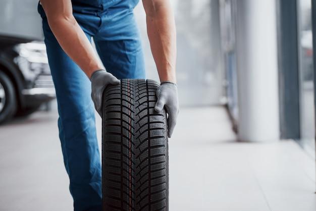 Механик держит шиномонтаж в ремонтном гараже. замена зимней и летней резины