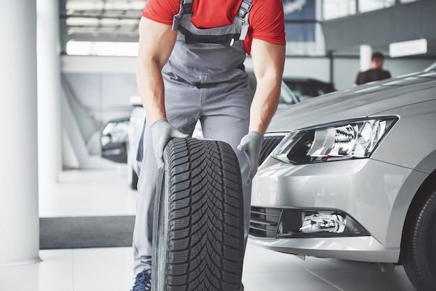 수리 차고에서 타이어 타이어를 들고 정비공. 겨울 및 여름 타이어 교체.