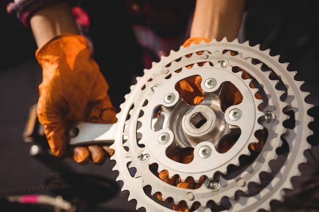 Meccanico in possesso di un ingranaggio della bicicletta