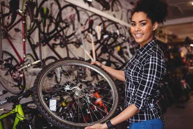Meccanico in possesso di una ruota di bicicletta