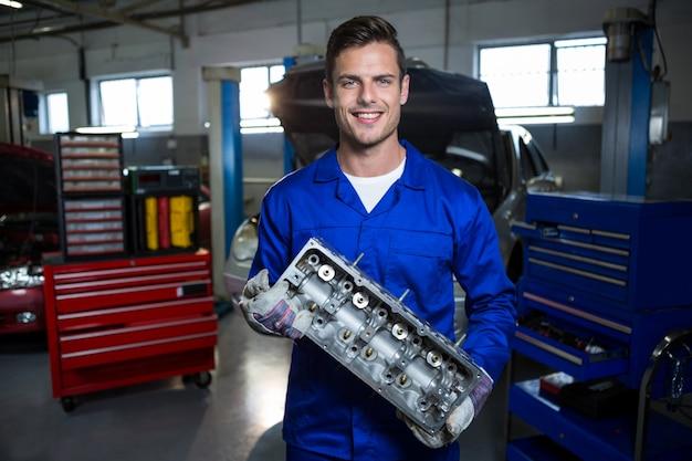 Meccanico auto motore tenendo