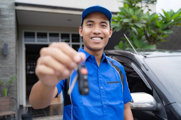 Mechanic holding car key and smiling