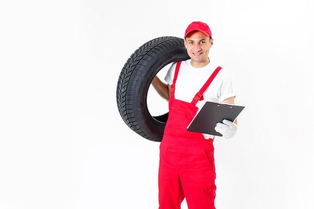 흰색 바탕에 자동차 타이어를 들고 정비사