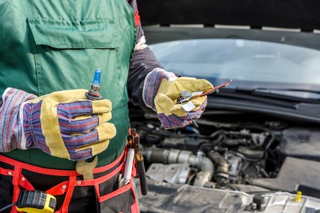 Механик держит лампу и кабели от фары автомобиля