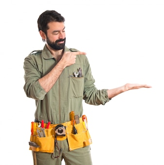 Mechanic holding something over white background