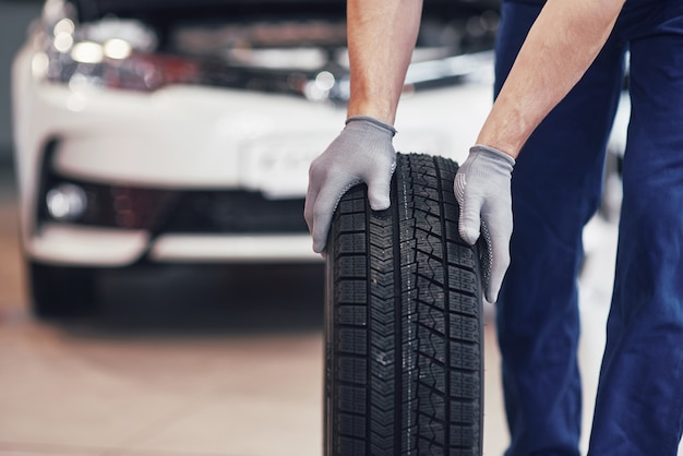 [Image: mechanic-holding-tire-tire-repair-garage...1596855884]
