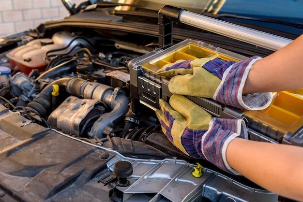 Mechanic holding tool box near broken car