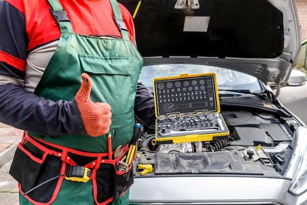 Механик держит ящик для инструментов возле разбитой машины