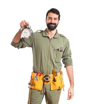 Mechanic holding vintage clock