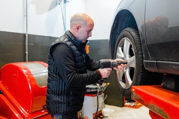 自動車修理工場の整備士が自動エレベーターの車両に車輪を付けている
