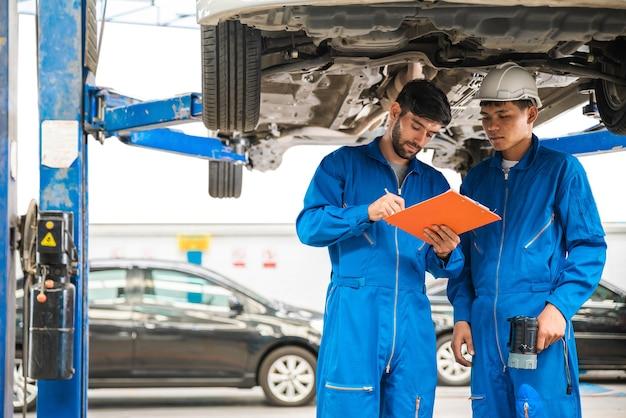 Механик в синей спецодежде осматривает днище автомобиля со своим помощником ремонт автомобилей