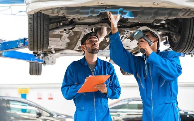 Механик в синей спецодежде осматривает днище автомобиля со своим помощником
