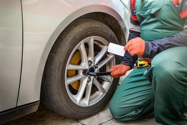 자동차 바퀴를 고정하는 가운의 정비공. 자동차 수리 기계공과 자동차 서비스 개념