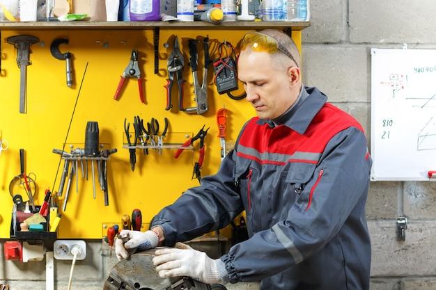Механик на рабочем месте делает ремонт дома строительства