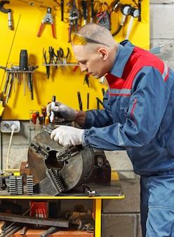 Механик на рабочем месте делает ремонт