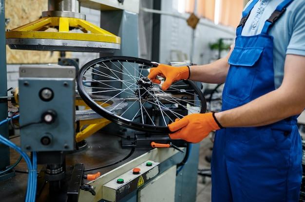 제복을 입은 정비공은 공장의 공작 기계 근처에서 자전거 바퀴를 보유하고 있습니다. 작업장에서 자전거 림 및 스포크 조립, 사이클 부품 설치, 현대 기술