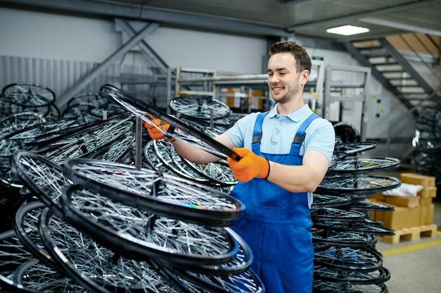 제복을 입은 정비공은 공장에서 자전거 바퀴를 보유하고 있습니다. 작업장에서 자전거 림 및 스포크 조립, 사이클 부품 설치, 현대 기술