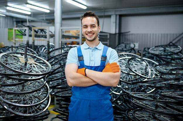 제복을 입은 정비공은 공장에서 자전거 바퀴를 보유하고 있습니다. 작업장에서 자전거 림 및 스포크 조립, 사이클 부품 설치