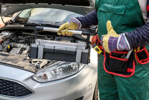 Механик в униформе позирует с ящиком для инструментов возле двигателя автомобиля