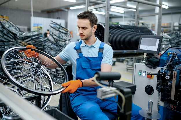 제복을 입은 정비공은 공장에서 자전거 바퀴와 함께 작동합니다. 작업장에서 자전거 림 및 스포크 조립, 사이클 부품 설치