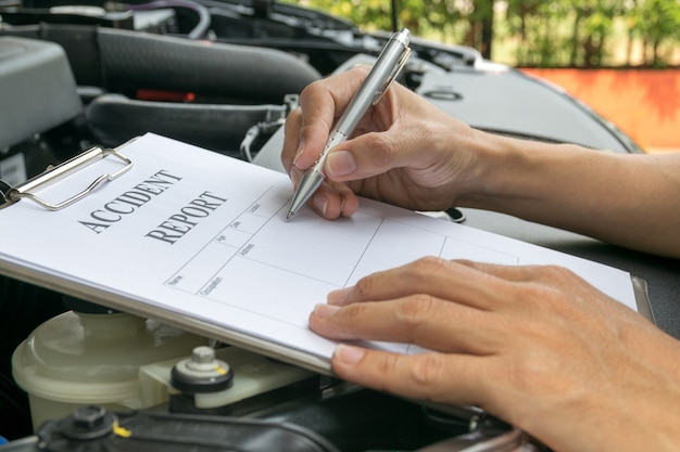 Mechanic inspecting damage car and filling in accident report form