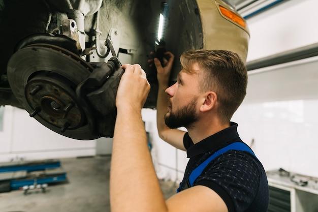 Mechanic inspecting wheel system