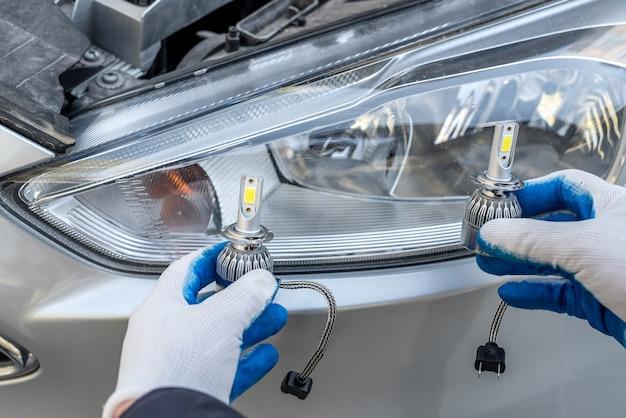 Mechanic installing changing modern halogen headlight bulb. lighting technology.