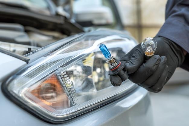 整備士が最新のハロゲンヘッドライト電球を交換して取り付けます。照明技術。