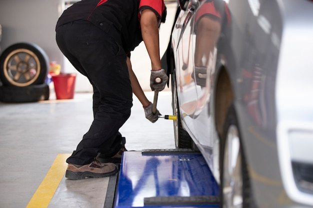 The mechanic is changing the car tires for those who use the tire center.