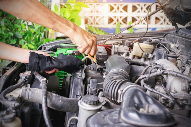 Mechanic is checking the level of engine oil from the engine oil level gauge of the car