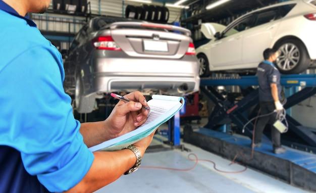 정비공은 차고에서 차량 하부의 수리 서비스를 확인하고 있습니다.