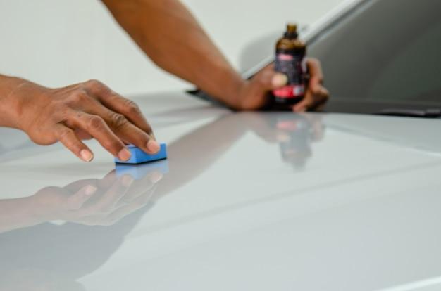 整備士は、車の傷を防ぐためにセラミックガラスをコーティングしています。