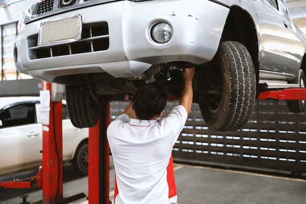 The mechanic is fixing the suspension of the car