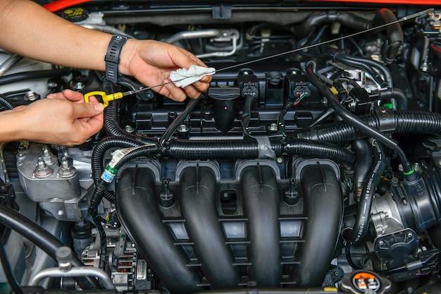 整備士がオイルレベルゲージを持って車のエンジンのオイルレベルをチェックしている