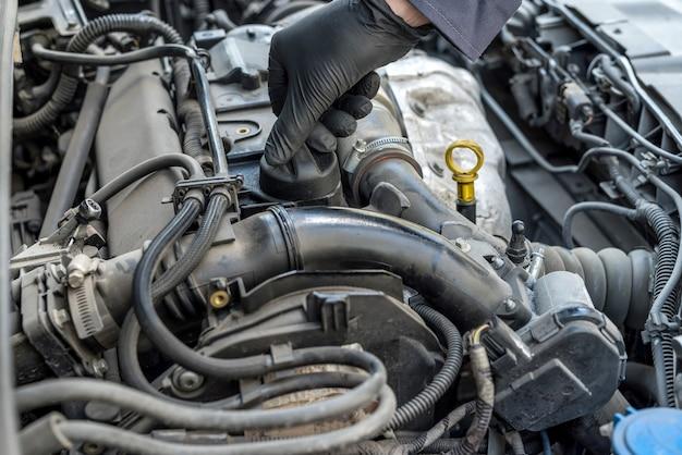 정비공이 자동차 엔진의 오일 교환을 위해 오일 캡을 열고 있습니다. 자동 서비스