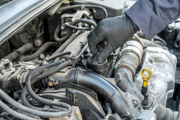 整備士は、自動車エンジンからのオイル交換のためにオイルキャップを開けています。オートサービス