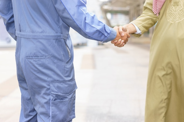 Mechanic is shaking hands with arabian client.